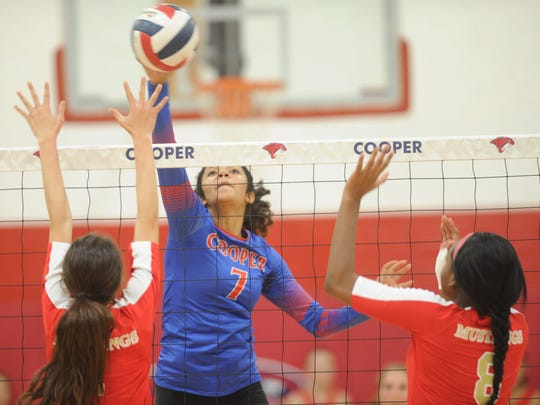 Cooper's Diamond Brown (7) hits the ball while Lubbock Coronado's Ayana Segrist (8) and a teammate defend. Lubbock Coronado sweeps Cooper in District 4-5A volleyball match