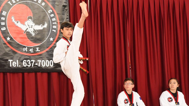 Guam Taekwondo Center junior blackbelt Micah Edusma executes the front kick as part of the Koryo, a Taekwondo blackbelt form, while competitors Joseph Schwartz and Alyxia Oftana look on.