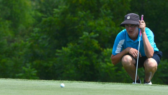 """Andrew Davis lines up a putt on the 17th green during"