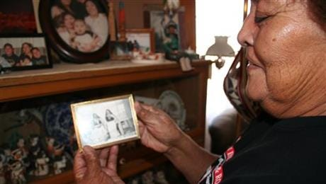 """Mary Lowden holds a photo of her mother and her aunt, both pottery makers, during a visit to her home at Acoma Pueblo, N.M. The pueblo is among the tribal communities featured in a new guidebook titled """"American Indians & Route 66."""""""