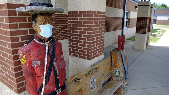 Someone has placed a mask on the Mapleton Mountie on the bench outside of Mapleton High School seen here on Thursday.