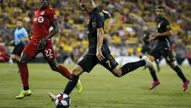 Crew midfielder Pedro Santos (7) crosses the ball against Toronto FC midfielder Richie Laryea during a game in August 2019.