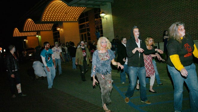 Zombies walk past the Coughlin-Saunders Performing Arts Center in downtown Alexandria at a past Zombie Walk.