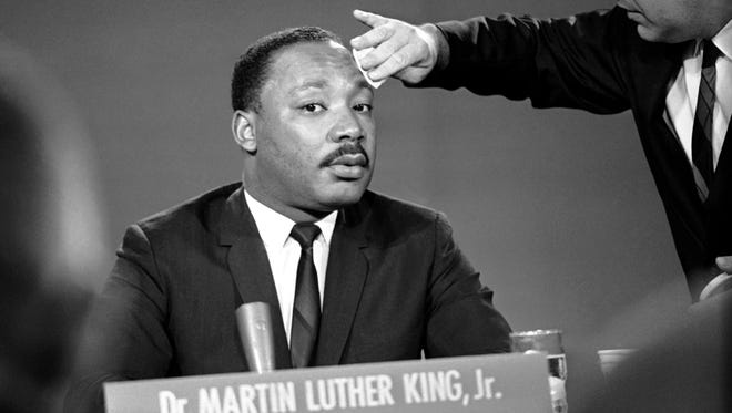 A makeup man puts powder on Martin Luther King's brow before a television program in Washington, Aug. 13, 1957.