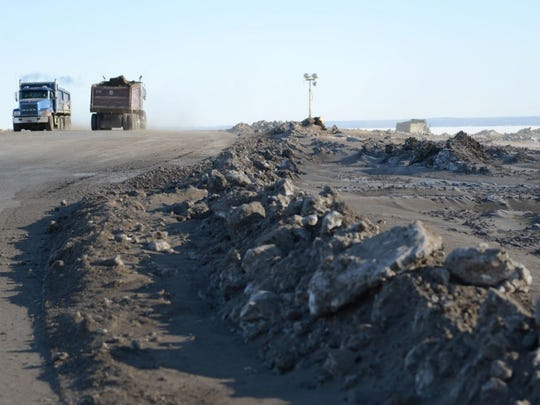 Dump trucks transport fill onto Renard Island last year.