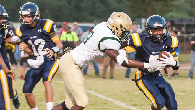 Acadiana's Bishop Breaux (3) tackle a Carencro ball carrier for a loss during the Rams' 48-13 win over the Bears earlier this season.
