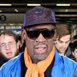 Former NBA star Dennis Rodman is surrounded by the media as he arrives at Beijing International Airport from North Korea on Monday.