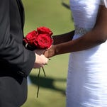 WEST PALM BEACH, FL - FEBRUARY 14: A couple holds hands as they are wed during a group Valentine's day wedding at the National Croquet Center on February 14, 2014 in West Palm Beach, Florida. The group wedding ceremony is put on by the Palm Beach Country Clerk & Comptroller's office and approximately 40 couples tied the knot.