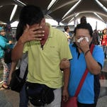 A woman wipes her eyes after walking out of the reception center and holding area for relatives and friends of passengers aboard a missing Malaysia Airlines plane, at Kuala Lumpur International Airport.