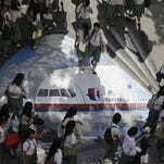 """Students from the Benigno """"Ninoy"""" Aquino High School walk on a mural depicting the missing Malaysia Airlines plane Tuesday, March 18, 2014 at their campus at Makati city, east of Manila, Philippines. Officials revealed a new timeline Monday suggesting the final voice transmission from the cockpit of the missing Malaysian plane may have occurred before any of its communications systems were disabled, adding more uncertainty about who aboard might have been to blame. The search for Flight 370, which vanished early March 8 while flying from Kuala Lumpur to Beijing with 239 people on board, has now been expanded deep into the northern and southern hemispheres. (AP Photo/Bullit Marquez) ORG XMIT: XBM102 (Photo: Bullit Marquez AP)"""