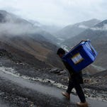 An Afghan villager carries election materials over his shoulders as he hikes back to his village along a country road high in the mountains of Shutul District in northern Afghanistan on April 4, 2014. An Afghan villager carries election materials over his shoulders as he hikes back to his village along a country road high in the mountains of Shutul District in northern Afghanistan on April 4, 2014.