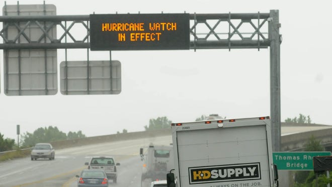 Vehicles travel across the Thomas Rhodes Bridge as rain falls early Thursday morning, July 3, 2014 in Wilmington, N.C. Residents along the coast of North Carolina are bracing for the arrival of the Hurricane Arthur, a category one storm. (AP Photo/The Star-News, Ken Blevins)