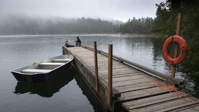 Morning mist lingers at Mountain Lake in Moran State Park in Washington state as Jennifer Imamura from Berkeley, Calif. (left) and Sylvia Yang of Anacortes, Wash. sit on the dock.