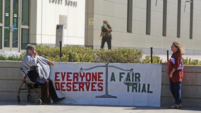 Jean McCann,left, and Melba Underbakke, executive director, Coalition for Civil Freedom, hold a banner outside the Federal Courthouse in Orlando, Fla., during opening statements Wednesday, March 14, 2018 in the trial of Noor Salman. Salman went on trial Wednesday in Orlando. The 31-year-old is accused of aiding and abetting her husband in his attack on the Pulse nightclub in June of 2016.