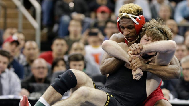 Cornell's Nahshon Garrett, left, controls Iowa's Cory Clark during the 133-pound championship match of the NCAA Division I Wrestling Championships, Saturday, March 19, 2016, in New York. Garrett won the match.