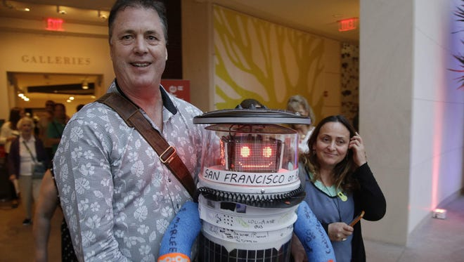 Co-creator David Harris Smith carries hitchBOT, a hitchhiking robot, during its' introduced to an American audience at the Peabody Essex Museum Thursday, July 16, 2015, in Salem, Mass. HitchBOT is set to embark on its' first cross-country hitchhiking trip of the U.S., after completing similar tips in Canada and Europe.