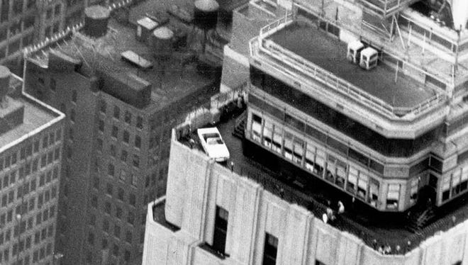 A 1966 Ford Mustang convertible is perched on a corner of the 86th floor observation deck of the Empire State Building in 1965