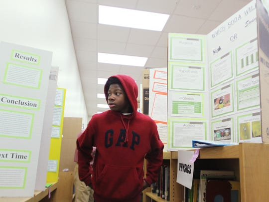 Eighth-grader Javonta Anderson looks at display boards during the science fair at Cobb Middle School on Friday.