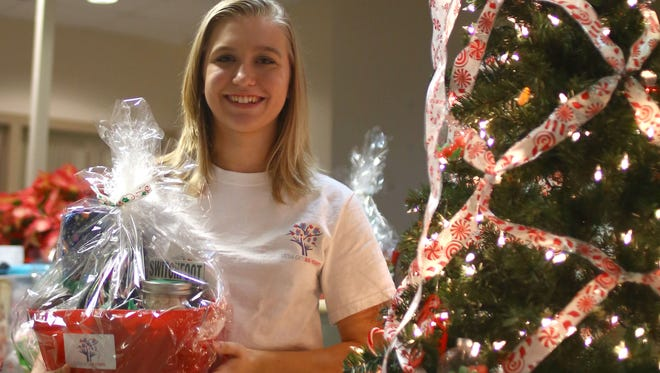 Jessica DeFrance, a senior at Classical Christian Academy in Fort Myers, stands with one of her gift baskets in the Neonatal Intensive Care Unit at Golisano Children's Hospital on Sunday, Dec. 19, 2016.
