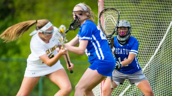 Stephen Decatur goalkeeper Rachel Florek (11) watches from the cage as midfielder Lexie Van Kirk (22) defends against Queen Anne's midfielder Abby Folker (12) in the Bayside Championship on Tuesday, May 10, at Queen Anne's High School in Centreville.