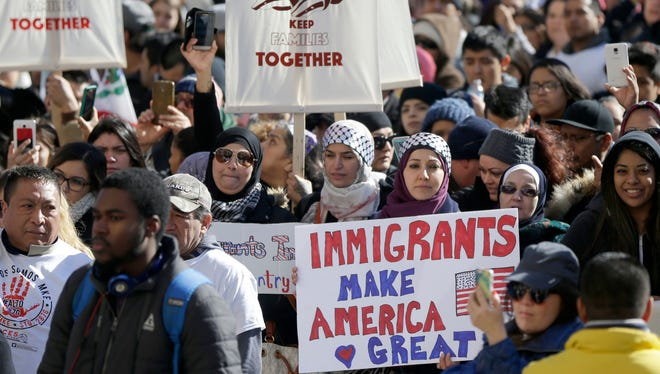 """Protesters hold an """"Immigrants make America Great"""" poster as attendees spoke from a podium Monday outside the Milwaukee County Courthouse."""
