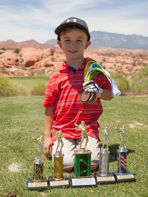 St. George's Trey Amico poses for a picture with some of the trophies that he has won. Trey is headed to the IMG Junior Worlds this weekend and will compete against the top golfers in the world. Amico is coached by his grandpa (Jay Don Blake) and will break Tiger Woods' record as the youngest competitor to play in the tournament.
