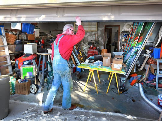 Doug Arnholter's studio is a small Northside garage filled with brushes, paint cans, Solo cups and random boxes everywhere.