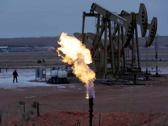Natural gas flares at a drilling site near Watford City, N.D., in 2015.