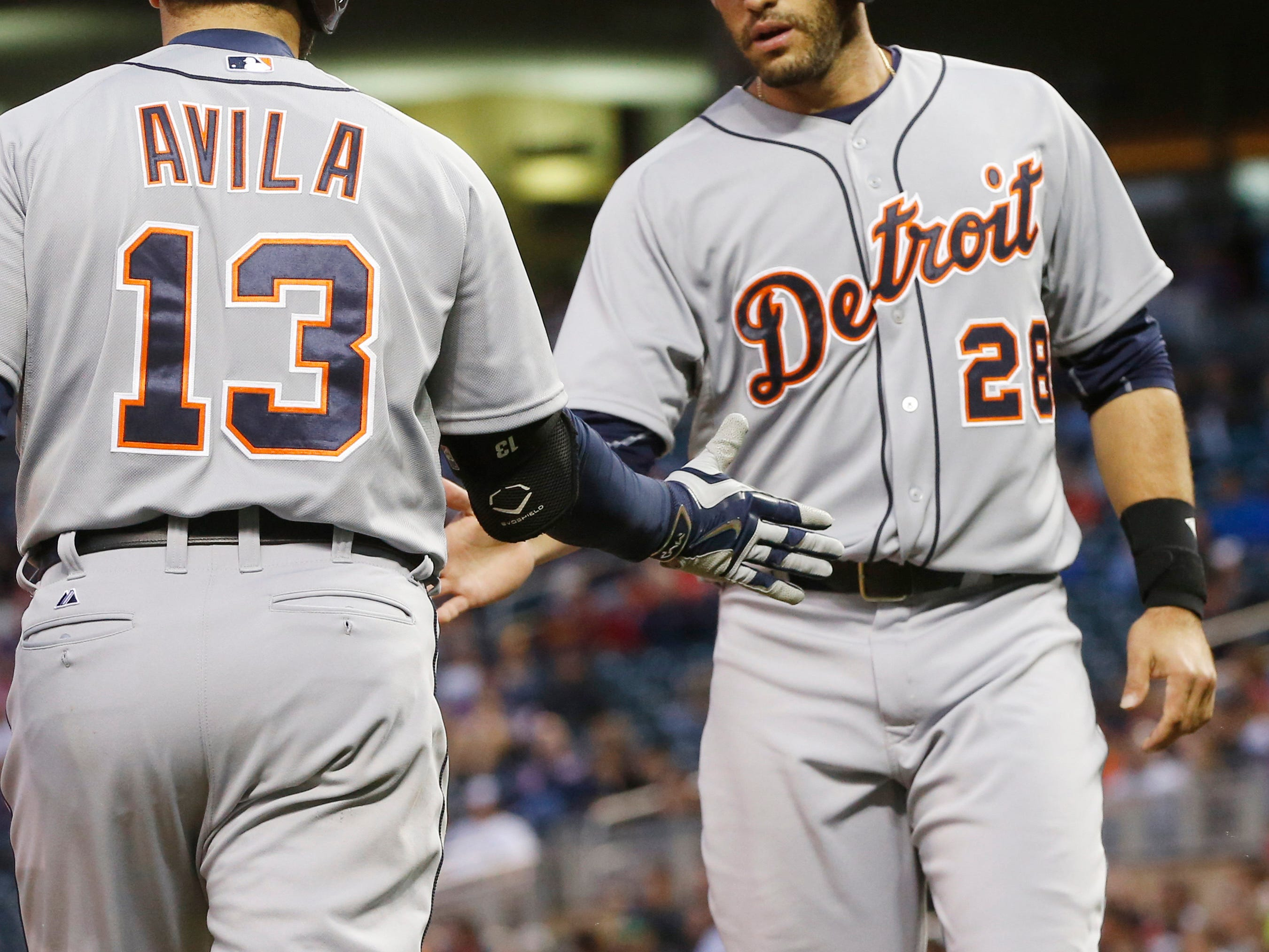 Detroit Tigers' J.D. Martinez, right, is congratulated by Alex Avila as he scores on a double by Yoennis Cespedes in the fourth inning of a baseball game off Minnesota Twins pitcher Mike Pelfrey, Tuesday, April 28, 2015, in Minneapolis. (AP Photo/Jim Mone)