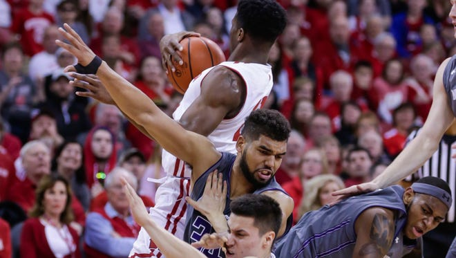 Wisconsin's Khalil Iverson grabs control of a loose ball and tries to avoid a tangle of players against Northwestern at the Kohl Center on Sunday.
