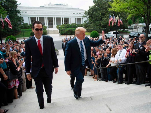Trump waves as he and Treasury Secretary Steven Mnuchin