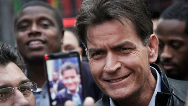 In this 2013 file photo, actor Charlie Sheen is mobbed for autographs and photos as he makes his way through Times Square in New York.