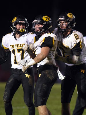 Adam Kain, left, and Nathan Lawler celebrate after Greg Nolder recovered a fumble during Tri-Valley's 27-18 win against Columbus Marion-Franklin last week in a Division III, Region 11 quarterfinal game. Nolder and Lawler have helped key a Scottie defense that has dominated in the fourth quarter.