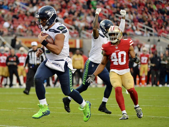 Seattle Seahawks quarterback Russell Wilson, left, runs into the end zone for a touchdown against the San Francisco 49ers during the first half of an NFL football game Sunday, Nov. 26, 2017, in Santa Clara, Calif. (AP Photo/Don Feria)