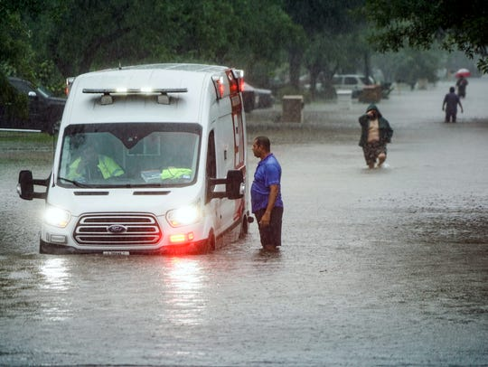 Residents of a McAllen, Texas, walk down a flooded