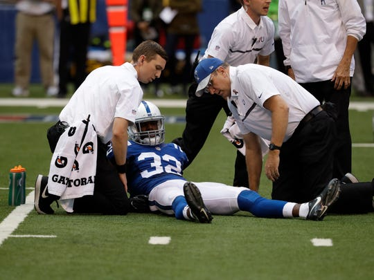 Indianapolis Colts free safety T.J. Green (32) is assisted after being injured during the first half against the Detroit Lions on Sunday.