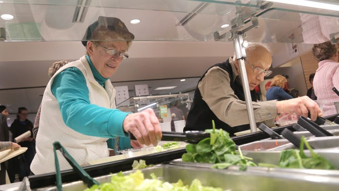 Marvel Broka and Emile John fill their plates from the salad bar at the campus cafeteria at Ohio State Mansfield/North Central State College on Thursday. The Area Agency on Aging along with the colleges, announced a partnership that day for providing meals to adults over the age of 60 when the campus kitchen is open.
