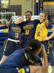 Marquette junior guard Olivia Moskari (13), senior center Shantelle Valentine (31) and junior forward Sandra Dahling pose as junior forward Erika Davenport snaps their picture at women's basketball media day Wednesday.