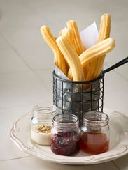 Churros served with a variety of sauces for dipping.