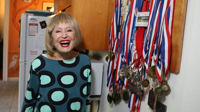 Ruth Kundsin of Quincy stands with her swimming medals in her home on July 24, 2020 - her 104th birthday. Lauren Owens Lambert/For The Patriot Ledger