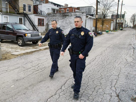 York City Police Officers Matthew Irvin, left, and Kyle Pitts walk an alley behind West Princess Street in York Tuesday Jan. 31, 2012.