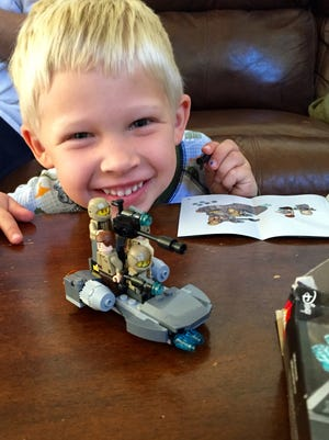 Young LEGO fan Scott Rough shows off his brick-building skills, and a smile.