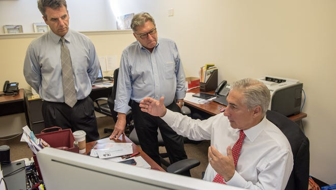Michael Vacca (seated) of Transword Business Advisors in Red Bank  discusses a new business listing evaluation with Christopher Zatorski (left) and Robert Hamecs.