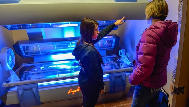 """Brittany Franklin (left) shows a tanning bed to Lisa Adams of Dingmans Ferry, Pa., at the 2014 opening of Boca Tanning Club, in Middletown, owned by MTV """"Jersey Shore"""" star Mike """"The Situation"""" Sorrentino. The salon has closed since then."""