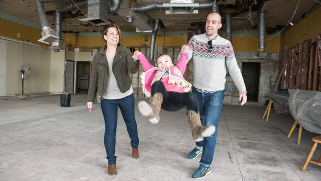 Booskerdoo owners James and Amelia Caverly swing their 2-year-old daughter Claire in the Asbury Park space that eventually will house their business.