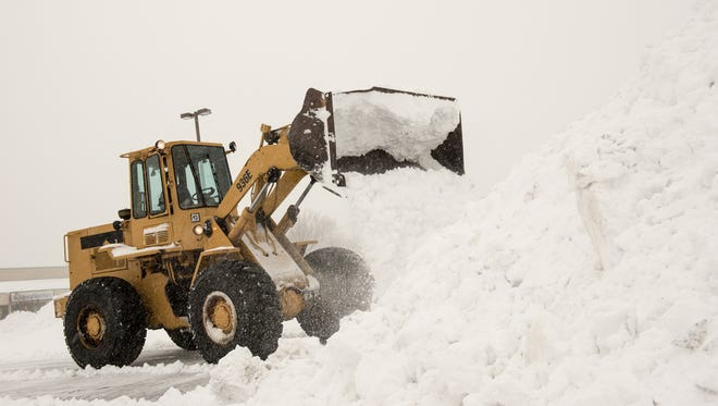A front-end loader moves snow in the Foodtown parking lot on Route 35 in Ocean Township.