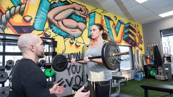 Billy Dawson (left) works with Jen Carducci, Holmdel, on curls at Evolve Training in Tinton Falls.