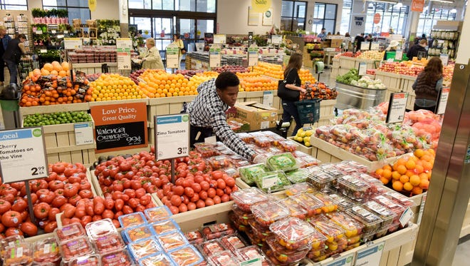 Whole Foods opened a new location in Wall. Dwayne Gudge stocks tomatoes in the produce section.