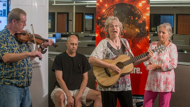 Singer and songwriter Karren Pell, third from left, brought along members of her band Old Alabama Town Revue Crue to perform Tuesday, July 26, 2016, in the Montgomery Advertiser newsroom.