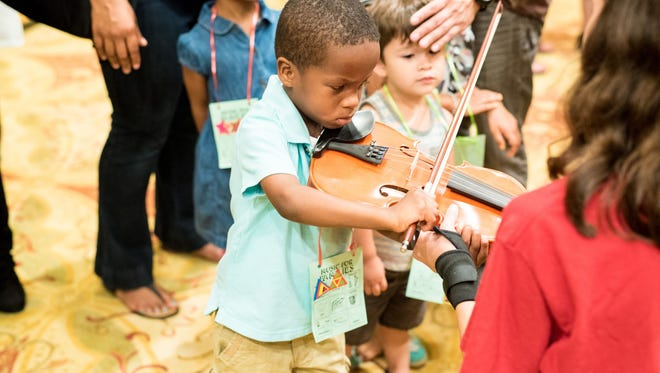 Children at the 2016 Music For Families event play with instruments.